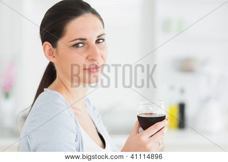 Smiling woman holding glass of red wine in kitchen