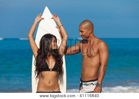 couple with surfboard on beach