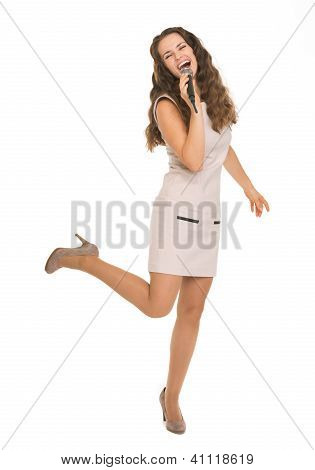 Full Length Portrait Of Happy Young Woman Singing With Microphon