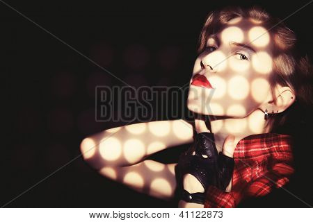 Portrait of a young fashionable model posing at studio with expression. Black background.