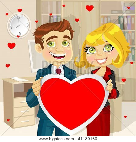 Cute businessman and business woman in office holding a valentine greeting Valentine's day