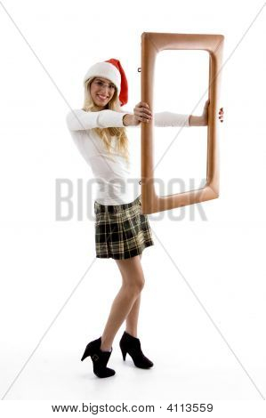 Side View Of Female Wearing Christmas Hat Holding A Frame