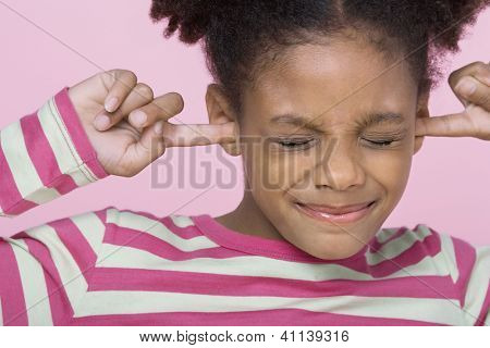 Girl with eyes closed putting fingers in ears