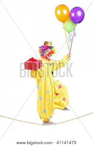 Full length portrait of a happy male clown walking on a rope with bunch of balloons and present isolated on white background