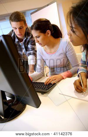 Grupo de estudantes trabalhando no laboratório de informática