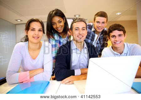 Teacher with students in class working on laptop