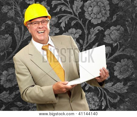 Happy Architect Man Holding Laptop Against Wallpaper
