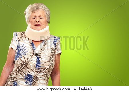 A Senior Woman Wearing A Neck brace On Green Background