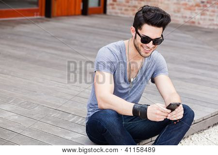 Attractive Young Male Model Texting On A Smartphone
