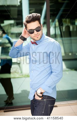 Attractive Young Male Model Posing Outdoors In Blue Shirt And Sunglasses