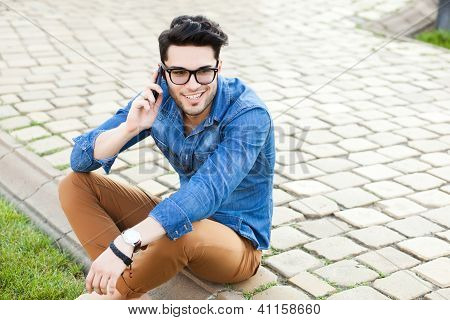 Handsome Young Man Talking On A Smartphone Outdoors