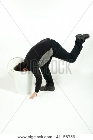 Man puts his head in the trash