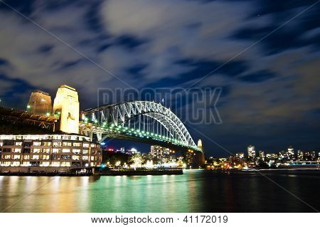 Moon lit Sydney Harbour Bridge with moving clouds in the sky