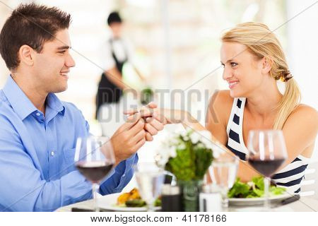 junger Mann setzen Verlobungsring auf seine Freundin, nachdem sie ja sagte