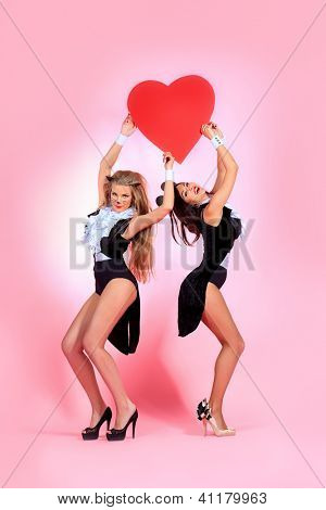 Two sexy playgirls in costumes of pussycat and a mouse alluring with red heart over pink background.