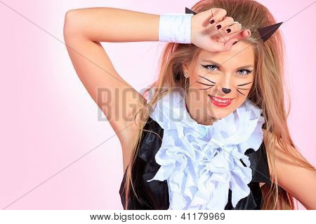 Portrait of a sexy playgirl in pussycat costume alluring over pink background.