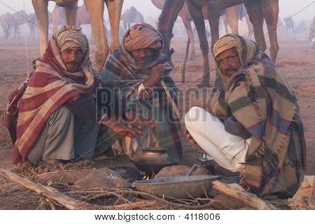 Men Keeping Warm Around An Open Fire