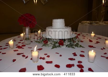 Candlelite Wedding Cake Surrounded By Rose Petals