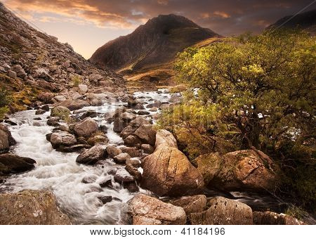 Waterfall In Mountains With Moody Dramatic Mountain Sunset Landscape