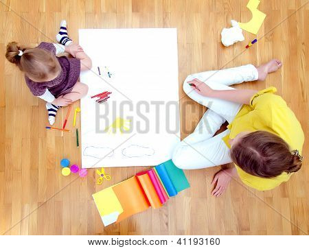 Young Woman And Little Girl Drawing Together Sitting On The Floor. Top View