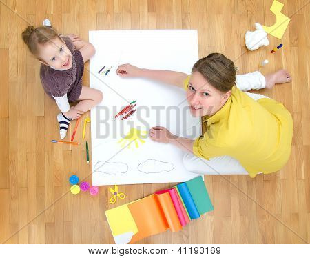 Young Woman And Little Girl Drawing Together Sitting On The Floor. Top View.