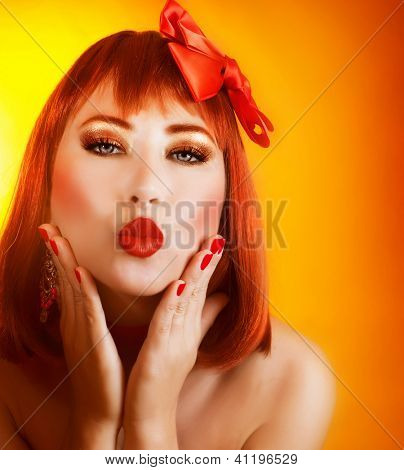 Picture of beautiful redhead girl with fashionable hairstyle and gorgeous red accessories isolated on orange background, holiday party, Valentines day, give kiss, red lipstick, love concept
