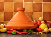 image of tagine  - Plain Maroccan Clay Tagine On A Terracotta Tile Background - JPG