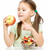 stock photo of licking  - Cute little girl choosing between apples and sweets licking her lips - JPG