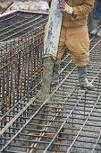 pic of formwork  - builder worker with tube from truck mounted concrete pump pouring cement into formwork reinforcement - JPG