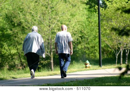 Seniors Walking On Park Pathway