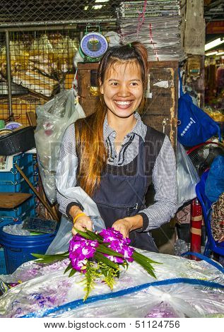 women sells fresh orchids at the morning market Pak Khlong Thalat