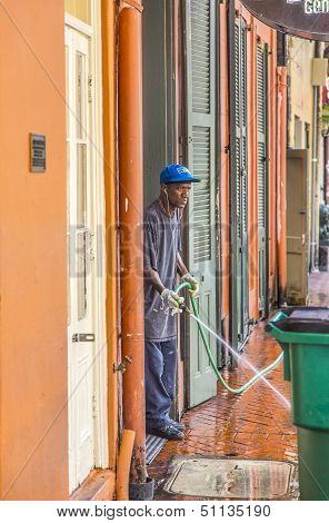 Man Cleans The Walkway In The Morning In New Orleans