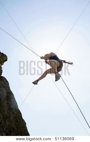 Low angle view of female rock climber rappelling against sky