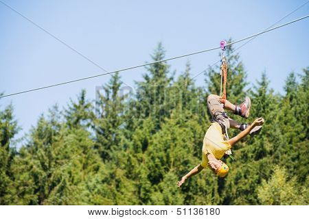 Full length of young man hanging upside down on zip line against trees in forest
