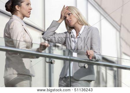 Joven empresaria discutiendo con colega en el pasamano de la oficina
