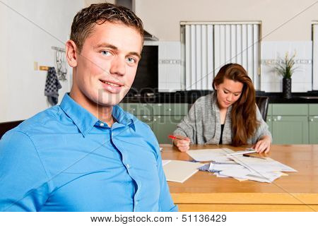 Young Man, sitting at the kitchen table, as he just finished getting her personal finances in order, with his girlfriend still  filing receipts, and signing giro transaction forms
