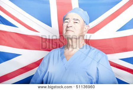 Portrait of a Senior Adult Surgeon in front of a British Flag
