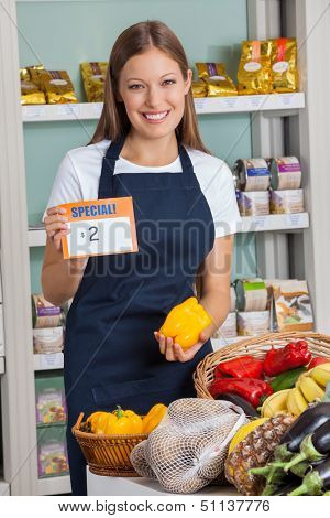 Portrait of young saleswoman holding pricetag and bellpepper in supermarket
