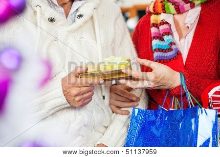 Midsection of senior couple holding Christmas present at store