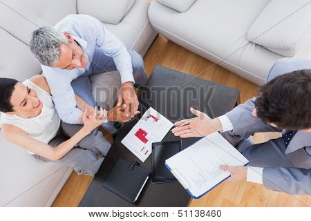 Salesman making his pitch to couple sitting on couch at home