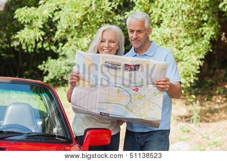 Smiling mature couple reading map by their cabriolet