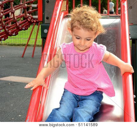 Young child, girl on a slide at the playground.