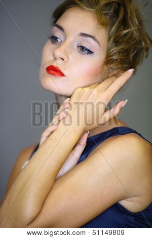 Portrait of a young woman with hands near the face