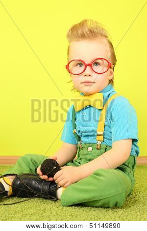 Mod little boy in a bright clothes and big red glasses sitting on the floor