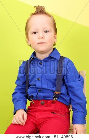 Mod boy in bright clothes sits on a background yellow and green wall