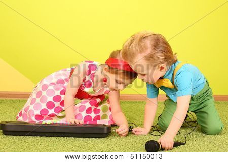 Little girl and boy in bright clothes connect a microphone to the toy piano