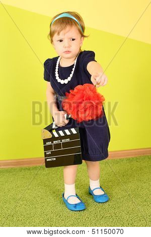 Little girl holding a clapstick in her hand and points a finger forward