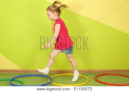 Running little girl with pigtails in a bright room, on the floor are the hoops