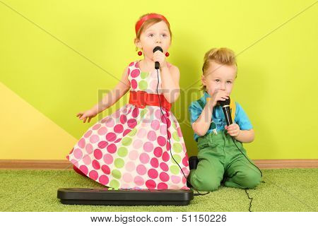 Mods girl and boy in bright clothes singing into a microphones