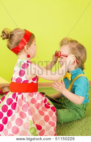 The girl in a bright dress puts on a big red glasses on the boy in the blue shirt and green jeans